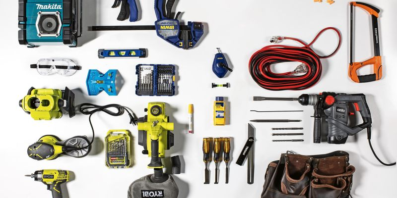 Flat-lay of various tools. These tools include a drills, sander, saw, toolbelt, earplugs, screwdrivers, power cords and clamps.
