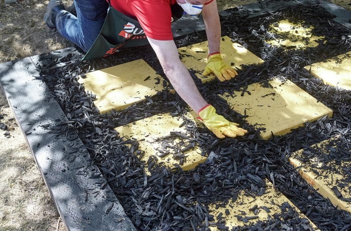 A person spreading black mulch between pavers laid out in a square on a bed of sand