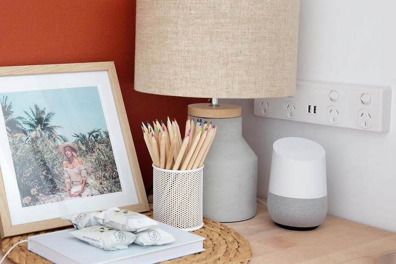 Hallway table with orange feature wall and accessible power points. The table has various objects on it such as an hourglass, a picture of a girl at the beach, a lamp, a tin of pencils and a Google home.